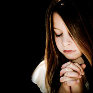 Jeune fille aux cheveux longs en train de prier