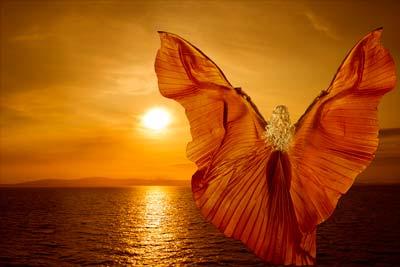 """Femme déployant ses """"ailes"""" au soleil couchant"""