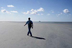 Homme marchant sur une plage immense