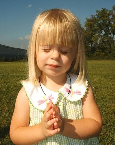 Petite fille les yeux fermés, les main en prières
