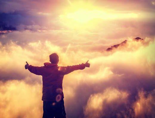 Jeune homme devant les nuages et face à la lumière de Dieu