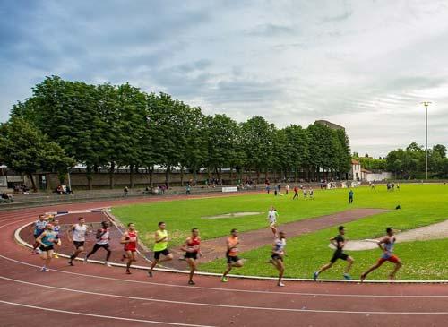 Hommes courant sur un stade lors d'une épreuve d'athlétisme