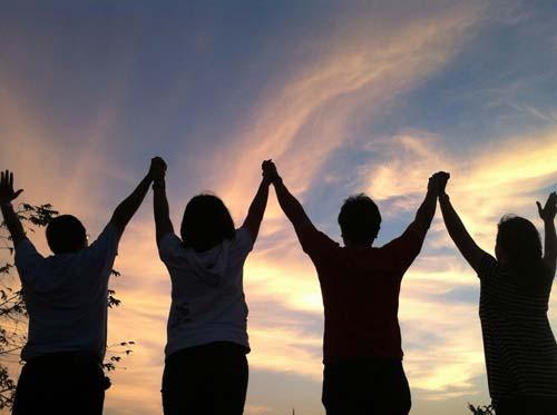 Hommes et femmes levant les bras au ciel à la gloire de Dieu