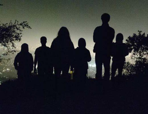 Groupe de marcheur dans la nuit devant les lumières de la ville
