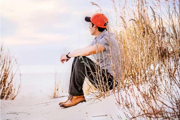 Homme assis sur le sable et qui regarde l'horizon en priant