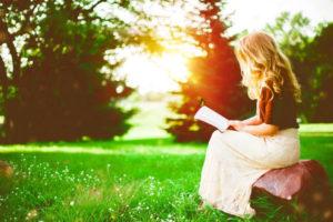 Jeune femme lisant la bible en pleine nature