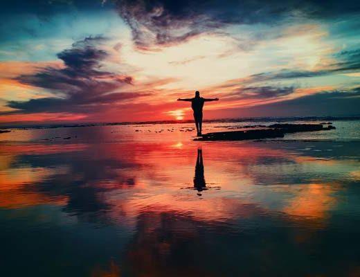 Homme priant devant le soleil qui se lève