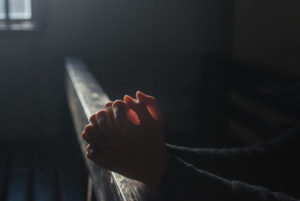 Mains jointes dans la lueur d'un vitrail