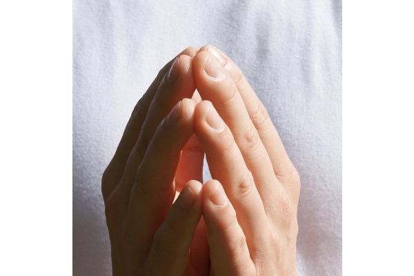 Mains en prière sur fond blanc