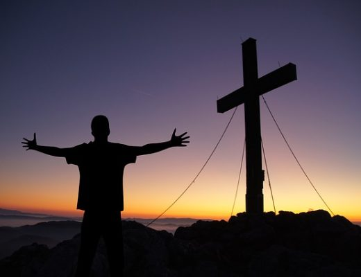 Homme priant devant la croix, au crépuscule