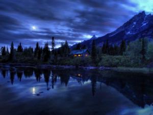 Maison dans la nuit aux fenêtres éclairées, au pied de la montagne